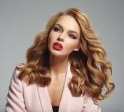 Het mooie jonge meisje met lang haar draagt roze jasje stock afbeeldingen