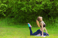Het mooie jonge meisje is met sporten, yoga, fitness op het strand door de rivier op een Zonnige de zomerdag bezig Royalty-vrije Stock Afbeelding
