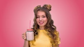 Het mooie jonge meisje met het stileren drinkt smoothies en glimlacht terwijl het onderzoeken van de camera op een roze achtergro stock video