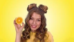 Het mooie jonge meisje met het stileren stelt met een sinaasappel knipoogt en glimlacht terwijl het onderzoeken van de camera stock video
