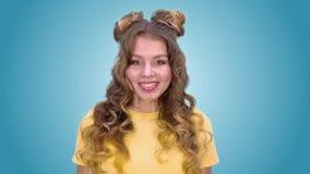 Het mooie jonge meisje met het stileren toont verrassing en glimlacht het onderzoeken van de camera stock video
