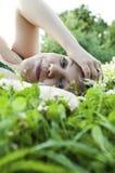 Het mooie jonge meisje ontspannen op een weide Stock Afbeelding