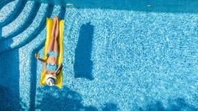 Het mooie jonge meisje ontspannen in zwembad, zwemt op opblaasbare matras en heeft pret in water op familievakantie stock fotografie