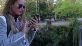 Het mooie jonge meisje schrijft een bericht om een smartphone tegen de achtergrond te gebruiken van een waterval in de zomer en stock footage