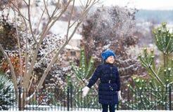 Het mooie jonge meisje spelen met sneeuw in park royalty-vrije stock fotografie