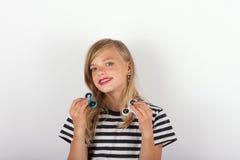 Het mooie jonge meisje spelen met twee friemelt spinners royalty-vrije stock fotografie