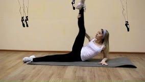 Het mooie jonge meisje in sportkleding doet oefeningen op uitbreiding het liggen stock videobeelden