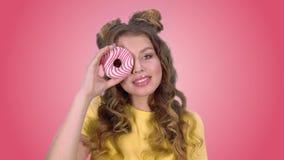 Het mooie jonge meisje stellen met een doughnut knipogen en het glimlachen het bekijken de camera op een roze achtergrond stock footage