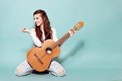 Het mooie jonge meisje stellen met gitaar Stock Afbeeldingen
