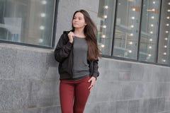 Het mooie jonge meisje stellen in warme kleren in de herfst Zwart jasje, rode jeans, grijze blouse Portret van een leuk donkerbru royalty-vrije stock afbeelding