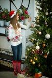 Het mooie jonge meisje verfraait Kerstmisboom Stock Foto's