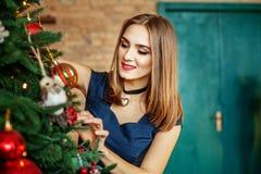 Het mooie jonge meisje versiert een Kerstboom Plaats voor insc Stock Foto