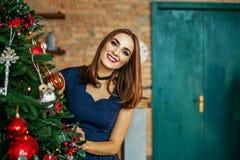 Het mooie jonge meisje versiert een Kerstboom Plaats voor tekst Co Stock Foto