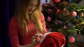 Het mooie jonge meisje zet op een Kerstmanhoed op haar favoriet stuk speelgoed draagt stock videobeelden