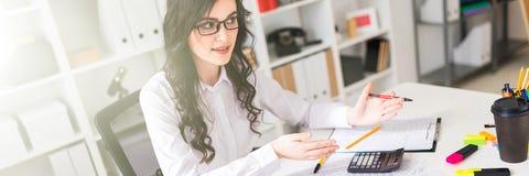 Het mooie jonge meisje zit bij de lijst in het bureau en voert onderhandelingen royalty-vrije stock afbeeldingen