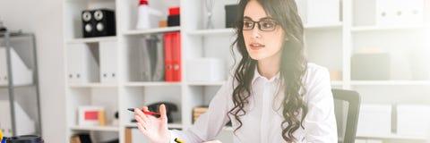 Het mooie jonge meisje zit bij de lijst in het bureau en voert onderhandelingen stock fotografie