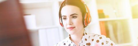 Het mooie jonge meisje zit in hoofdtelefoons bij bureau in bureau, houdt een notitieboekje in haar hand en drukken op het toetsen royalty-vrije stock afbeeldingen