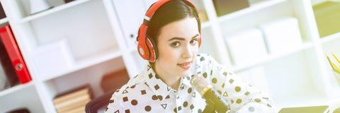 Het mooie jonge meisje zit in hoofdtelefoons en met een microfoon bij het bureau in het bureau royalty-vrije stock foto