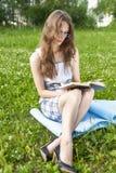 Het mooie jonge model die van het studentenmeisje een kleding en glazen s dragen stock foto