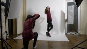 Het mooie jonge model en de fotograaf koppelen het flirten op het werk tijdens een zitting van de fotospruit stock footage