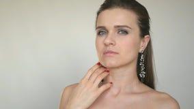 Het mooie jonge model stelt voor de camera op een witte achtergrond, strijkend op het gezicht royalty-vrije stock afbeelding