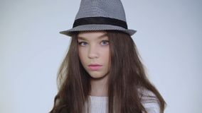 Het mooie jonge modelliftenhoofd in hoed en bekijkt enigmatically camera stock footage
