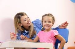 Het mooie jonge moeder schilderen met dochter stock afbeelding