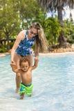 Het mooie jonge moeder spelen met haar zoon op de pool royalty-vrije stock afbeeldingen