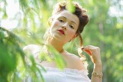 Het mooie jonge mollige meisje stellen in middeleeuws retro korset en witte uitstekende lingerie in het bos royalty-vrije stock foto