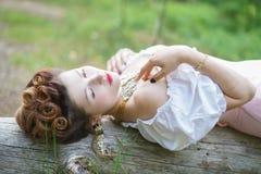 Het mooie jonge mollige meisje stellen in middeleeuws retro korset en witte uitstekende lingerie in het bos stock afbeelding