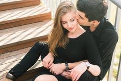 Het mooie jonge multiraciale paar, studentenpaar in liefde, zit houten trap in de stad De mooie Turkse donkerbruine kerel koester royalty-vrije stock afbeeldingen