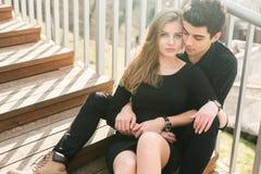 Het mooie jonge multiraciale paar, studentenpaar in liefde, zit houten trap in de stad De mooie Turkse donkerbruine kerel koester stock foto's