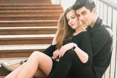 Het mooie jonge multiraciale paar, studentenpaar in liefde, zit houten trap in de stad De mooie Turkse donkerbruine kerel koester stock afbeeldingen