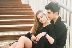 Het mooie jonge multiraciale paar, studentenpaar in liefde, zit houten trap in de stad De mooie Turkse donkerbruine kerel koester royalty-vrije stock foto's