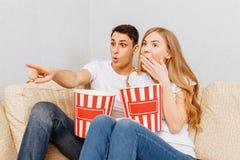 Het mooie jonge paar, de man en de vrouw, horlogefilms en eten popcorn, thuis zittend op de laag stock foto's