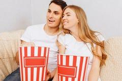 Het mooie jonge paar, de man en de vrouw, horlogefilms en eten popcorn, thuis zittend op de laag royalty-vrije stock foto's