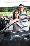 Het mooie jonge paar glimlacht en bekijkt camera terwijl het leunen op hun nieuwe auto in een motorshow De mens houdt autosleutel royalty-vrije stock afbeelding