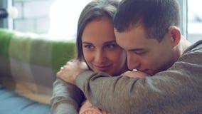 Het mooie jonge paar, leidt een prettig gesprek, omhels zacht, zittend bij het venster stock videobeelden