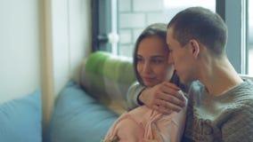 Het mooie jonge paar, leidt een prettig gesprek, omhels zacht, zittend bij het venster stock footage