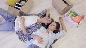 Het mooie jonge paar ontspannen die op de vloer na zich het bewegen aan nieuwe flat liggen stock videobeelden