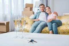 het mooie jonge paar ontspannen op laag terwijl zich het bewegen in nieuw huis met champagneglazen en sleutels royalty-vrije stock fotografie