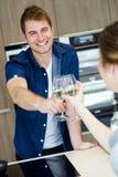 Het mooie jonge paar roosteren met witte wijnglazen in de keuken Royalty-vrije Stock Afbeelding