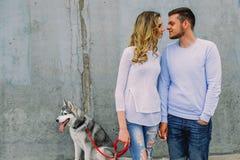 Het mooie jonge paar spelen met een hond schor in een park Summe Royalty-vrije Stock Afbeeldingen