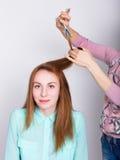Het mooie jonge redhaired model in salon, kapper doet een kapsel maakt de haaruiteinden met schaar in orde Royalty-vrije Stock Foto