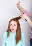 Het mooie jonge redhaired model in salon, kapper doet een kapsel maakt de haaruiteinden met schaar in orde Stock Afbeeldingen