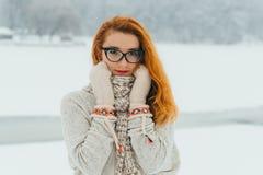 Het mooie jonge rode meisje in glazen is verpakt die met sjaal en het dragen van handschoenen in het bos met sneeuw wordt behande Stock Fotografie
