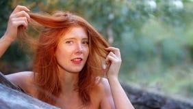 Het mooie jonge sexy roodharige meisje geniet van glimlachend gelukkig het spelen bij haar mooie rode haren stock foto's