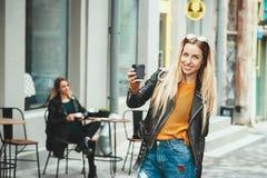 Het mooie jonge stedelijke vrouw dragen in modieuze koffie houden vormt en kleren die terwijl het lopen langs de straat glimlache Stock Foto's