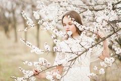 Het mooie jonge tedere meisje in bloesemtuin op een de lentedag, bloembloemblaadjes die van de boom vallen, sloot haar ogen en he royalty-vrije stock fotografie