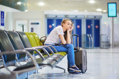 Het mooie jonge toeristenmeisje met rugzak en draagt bagage in internationale luchthaven Stock Afbeelding
